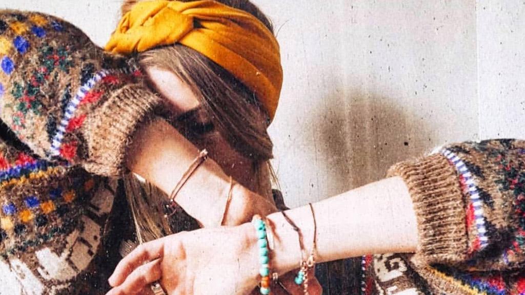 Junge Frau mit Stirnband, Schmuck und buntem Pullover